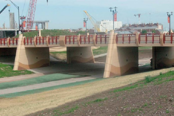 An overpass over a culvert with stained concrete elements.