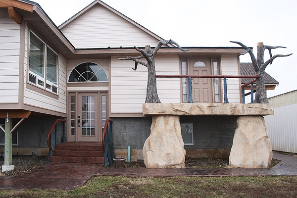 A unique home with a concrete tree out front on a large concrete deck.