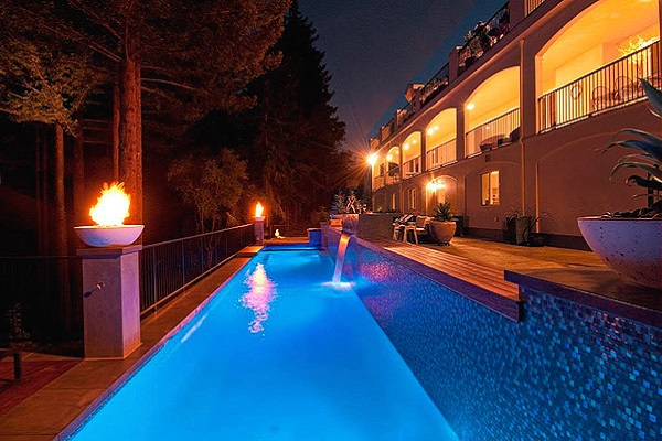Outdoor space that is lit up for the night with torches and lights that reflect off of the waterfall and the pool below.
