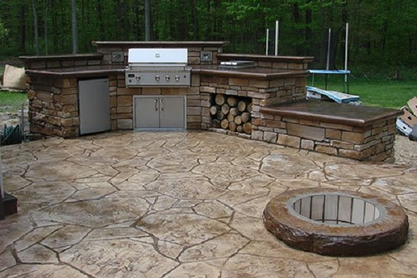 An outdoor kitchen with a concrete countertop and a large grill and a place to store logs for the firepit.