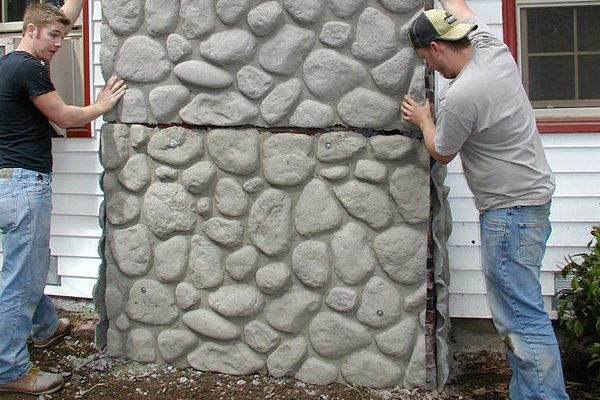 Two men placing concrete veneer panels that look like they are placed river rock.