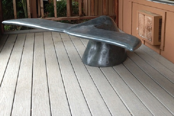 A concrete bench that is modeled after a whale's tail