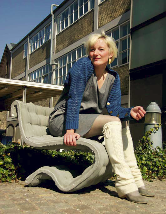 A woman sits on a chair that has been fabric formed.
