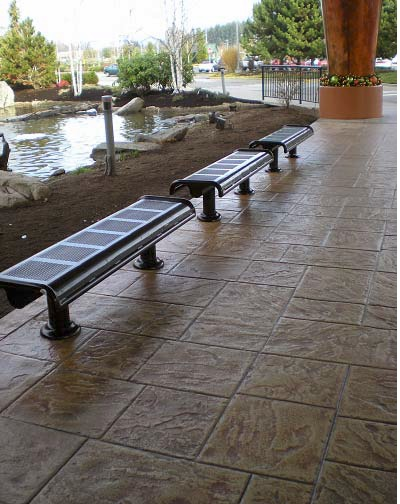 Stamped and stained concrete with benches makes for an appealing waiting area in a park setting.