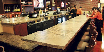 A concrete bartop in a restaurant in San Diego serves its customers well
