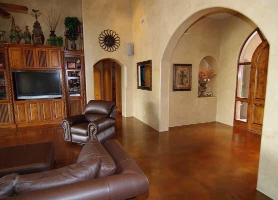 Stained concrete living room with dark brown leather furniture.