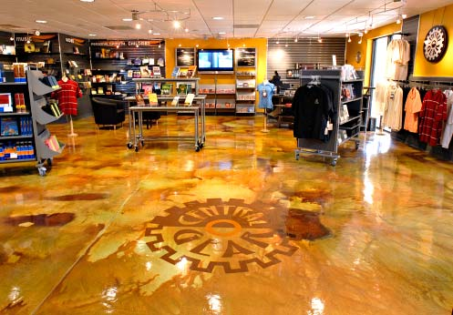Retail application of a concrete overlay that has been colored using acid stains and then a stencil applied in a gear shape.