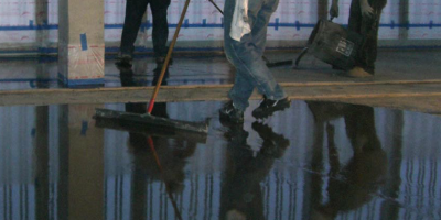 Men spreading a cementitious overlay in a large building.