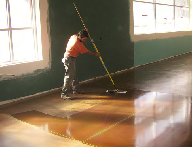 Contractor applies floor coating with a large broom.