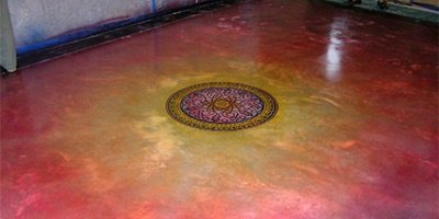 Pink and yellow concrete dye was created to emphasize the flower in the middle of this floor.