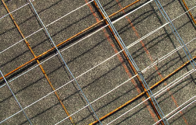 Typical welded wire fabric — a tight grid of galvanized utility fencing, with the roll of fencing material tied to the flat sheets of welded wire.