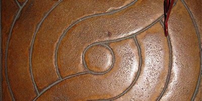 Grooved concrete in a circular pattern and stained with brown stain.