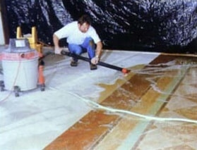 Removal of excess concrete stain prior to neutralizing the concrete overlay.