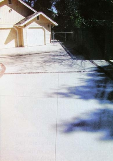 Long driveway with decorative concrete overlay covering a cracked slab.