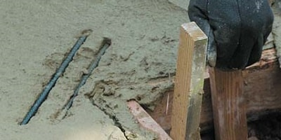 Placing two pieces of re-bar into freshly poured concrete in areas that are known to crack.