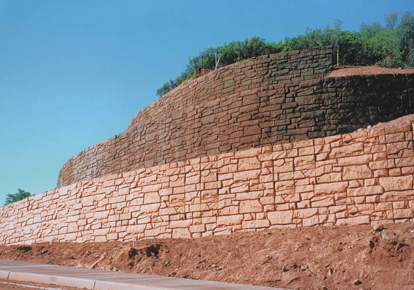Larrge colored retaining wall built with formliners and colored to blend in naturally to its surrounding.