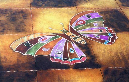 A colorful butterfly was engraved onto a concrete floor and enhanced using stains and dyes.