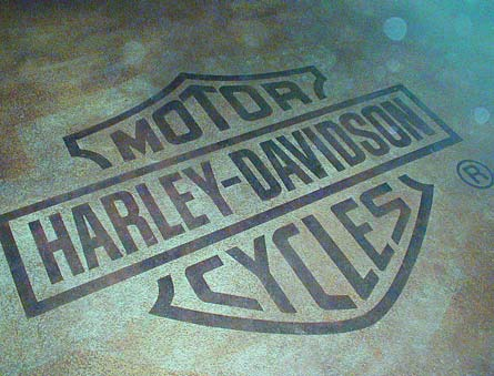 Popular brand, Harley Davidson Cycles logo was engraved on a simple gray background.