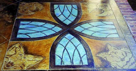 A geometric rendering of stained glass windows done with engraved concrete and stain.