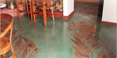 A floor in a beach house that has been stamped with custom seaweed stamps.