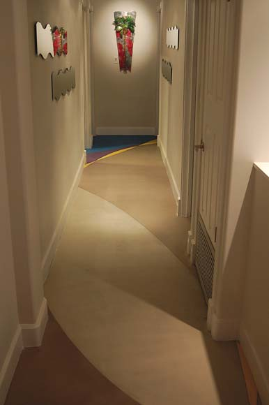 Concrete overlay in a hallway with sweeping colored patterns.