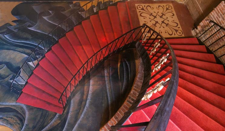 Red carpeted stair case looks to keep winding down with this 3d artwork on an overlay.