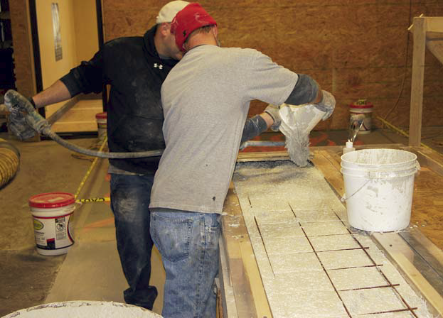 Jason Geiser and team member create the forms and fill them with concrete for the skateboard steps.
