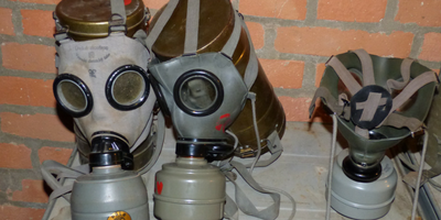 Three gas masks lined up on a brick wall.