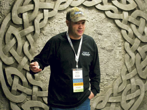 Nathan Giffin stands in front of his carved concrete wall.