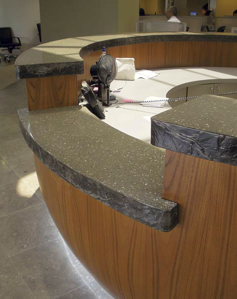 A concrete countertop flanks this reception area. The concrete is colored in charcoal with white flecks.