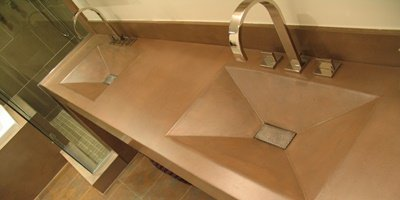 A bathroom vanity made with concrete and a double sink feature.