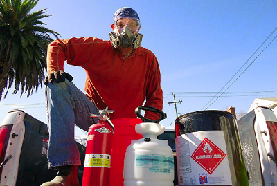 I now dress appropriately when spraying flammable solvents: long-sleeved shirt and pants, and headscarf, in natural fibers; respirator and goggles; leather boots and gloves. There's a bucket and rag in case the hose bursts and an appropriate fire extinguisher and water hose with a trigger nozzle.