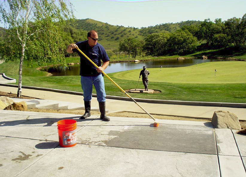 Glen Roman applies an acid wash over the freshly placed concrete.
