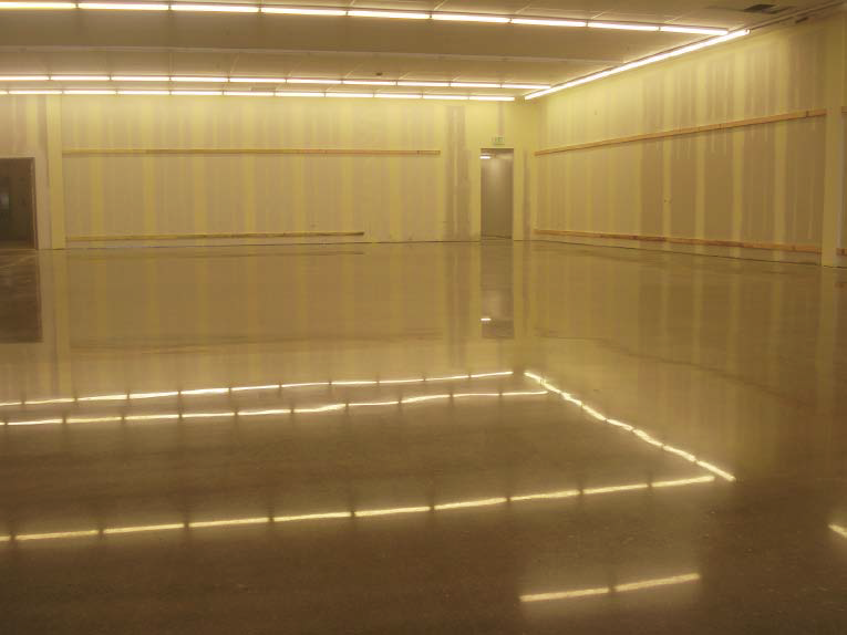 A high-gloss concrete floor that is reflecting the overhead lights.