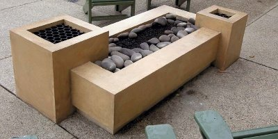 Rectangular concrete fire pit with round river rock surrounding fire tube.