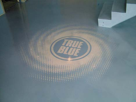 True Blue logo colored into a concrete floor.