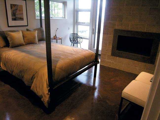 Shining concrete floor in a lovely bedroom setting with a fireplace.