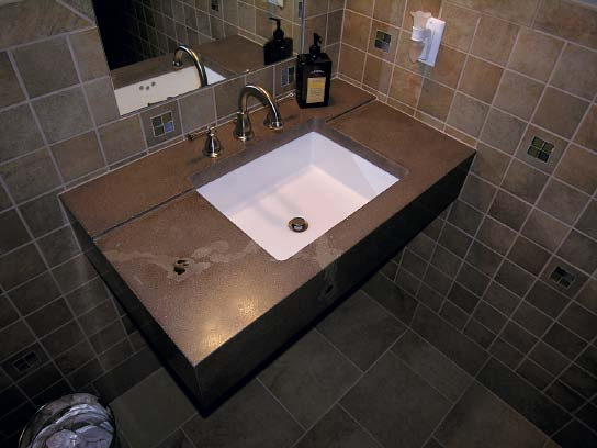 Dark gray floating concrete sink in a restroom by Troy Lemon.