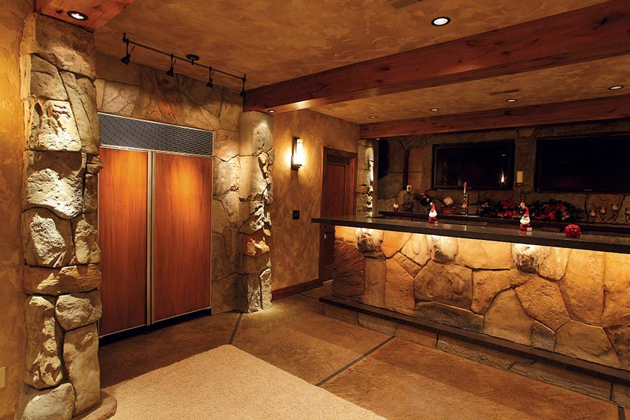 Large kitchen sporting vertical carved concrete rocks surrounding over sized refrigerator.