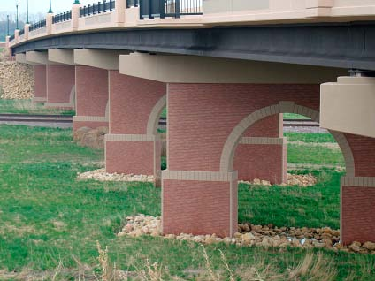 This bridge, which carries 195th Street across the Canadian Pacific Railroad tracks in Farmington, Minn., is supported by poured-in-place, arched concrete piers with integrally cast thin brick and simulated stone rustications.