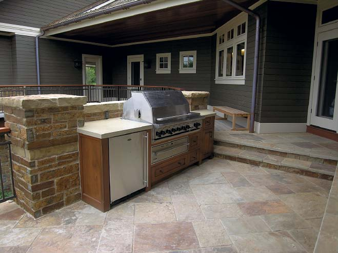 Outdoor kitchen with a BBQ surrounded by vertical concrete and concrete countertops.