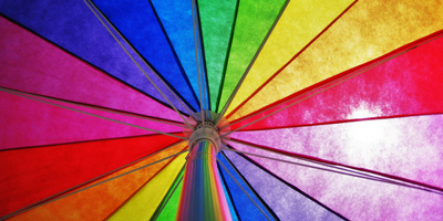 Looking up into a rainbow colored umbrella