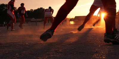 Football players practicing in the sunset.