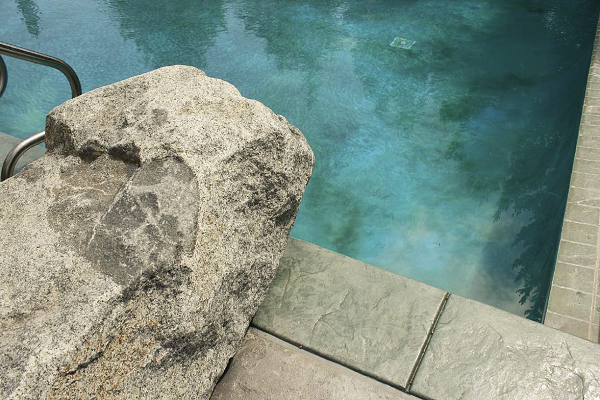 A faux rock up against the edge of the pool water acts as a diving board from the pool deck.