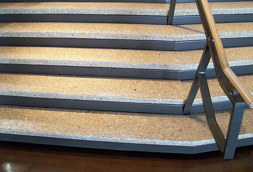 Textured two toned concrete stair case with wood and steel hand rail.