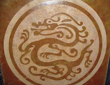 Chinese dragon symbol stand blast stenciled into concrete and then stained.