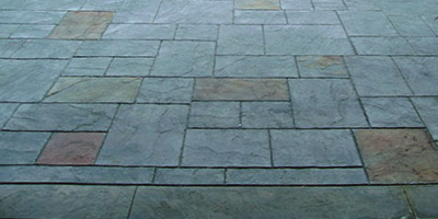 Dark natural stone look patio made from stamping and staining concrete and the recipe on how to recreate.