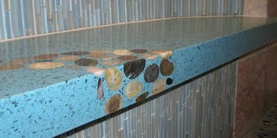 Originally designed for a shower bench installation, this striking river-themed countertop application features a dazzling blue-colored mix with glass aggregate and gorgeous river stone detailing.