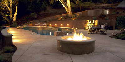 High end pool deck lit by night lights and a glowing fire pit.
