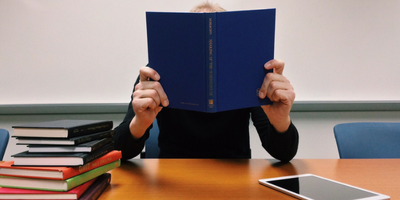 Person holding a blue book in front of their face with a stack of books and a tablet next to them.